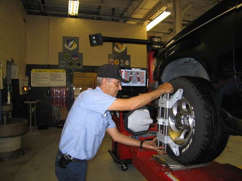technician aligns wheel